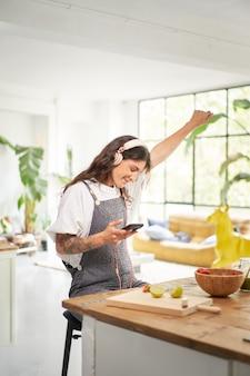 Gioioso giovane vincitore a casa che celebra il concetto di vittoria mobile studente euforico che riceve sms