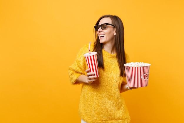 Gioiosa giovane donna in occhiali 3d imax che guarda da parte guardando film film tenere secchio di popcorn, tazza di plastica di cola o soda isolato su sfondo giallo. persone sincere emozioni nel cinema, nello stile di vita.