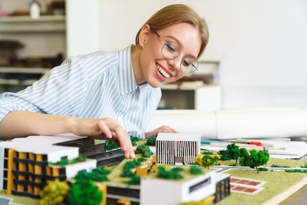 Gioiosa giovane donna architetto in occhiali che progetta bozza con modello di casa e seduta sul posto di lavoro