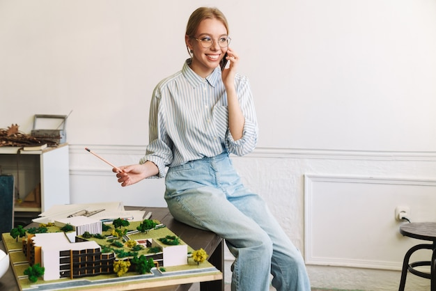 Gioiosa giovane architetto che parla al cellulare durante la progettazione di un progetto con un modello di casa sul posto di lavoro