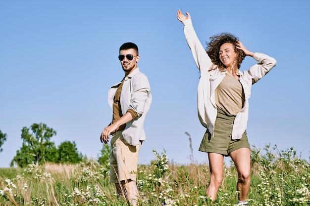 Gioiosa giovane donna che balla nell'erba verde contro il cielo blu ed esprime gioia mentre suo marito è vicino