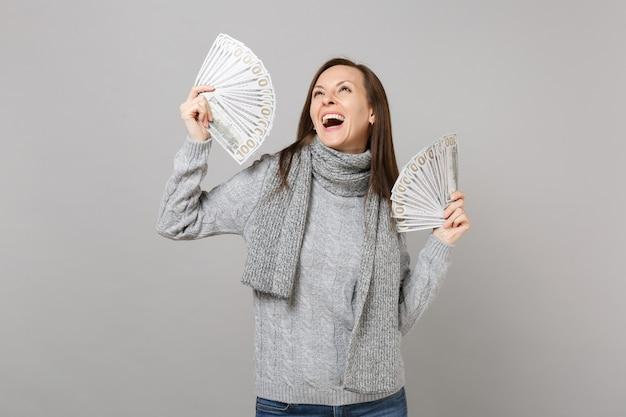 Gioiosa giovane donna in maglione grigio sciarpa guardando in alto, tenendo un sacco di banconote in dollari, denaro contante isolato su sfondo grigio. stile di vita sano, emozioni delle persone, concetto di stagione fredda.