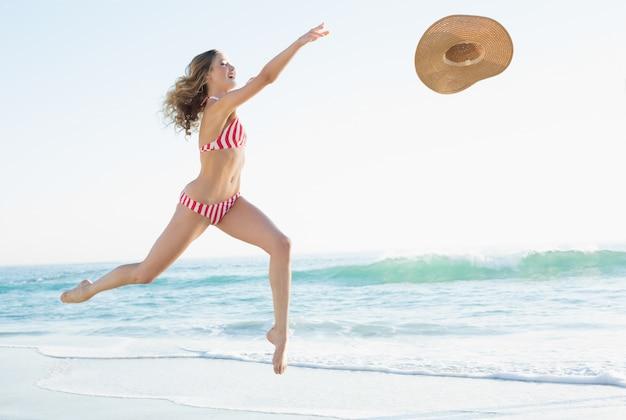 Gioiosa giovane donna che salta sulla spiaggia