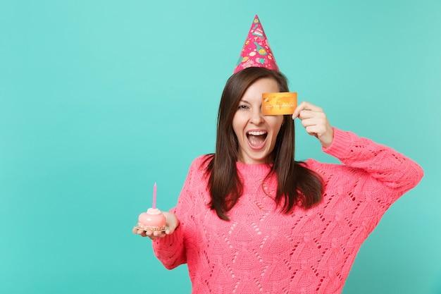 Gioiosa giovane donna in maglione rosa lavorato a maglia, cappello di compleanno che tiene in mano la torta con la candela, coprendo l'occhio con carta di credito isolata su sfondo blu muro. concetto di stile di vita della gente. mock up copia spazio.