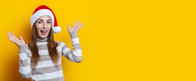 Gioiosa giovane donna con il cappello di babbo natale su uno sfondo giallo. bandiera.