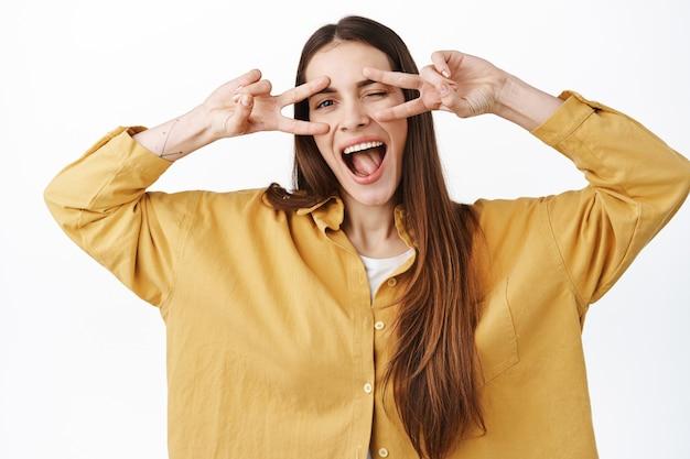 La giovane donna gioiosa mostra i segni della discoteca kawaii sugli occhi, strizza l'occhio e sorride, rimanendo sul lato positivo brillante, esprime felicità e gioia, in piedi sul muro bianco