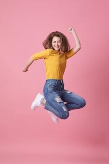 Giovane donna allegra in camicia gialla che salta e che celebra