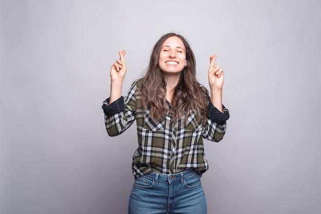 Joyfull giovane donna sorridente e in piedi con il dito incrociato sul muro grigio