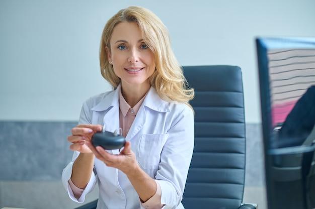 Gioioso otorinolaringoiatra esperto che dimostra gli aiuti per non udenti davanti alla telecamera
