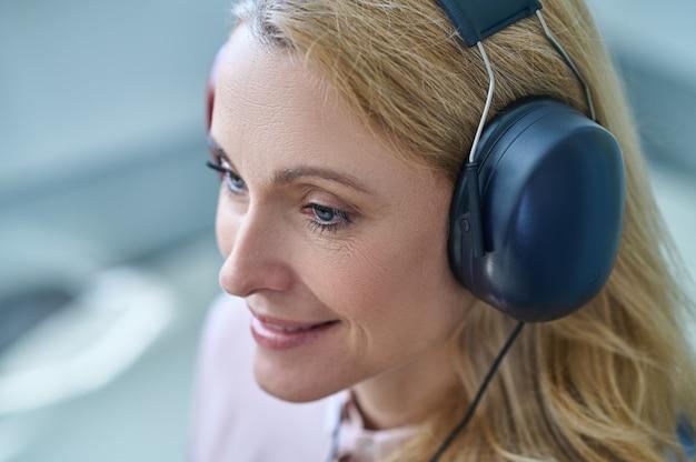 Paziente gioiosa che sogna ad occhi aperti durante una procedura di screening dell'udito