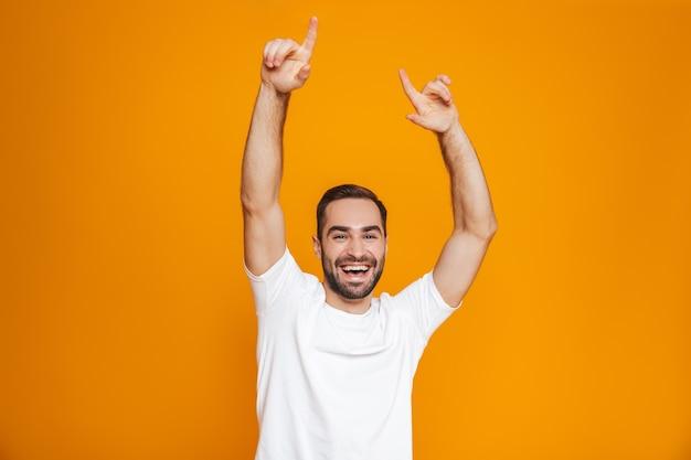Uomo gioioso con barba e baffi sorridente in piedi, isolato su giallo