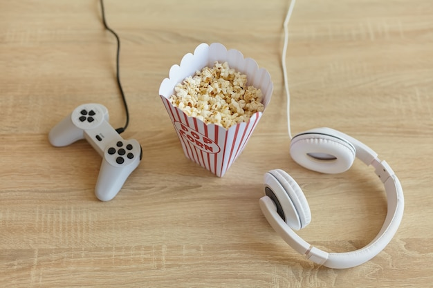 Joystick, console di gioco, cuffie e popcorn sul tavolo in soggiorno