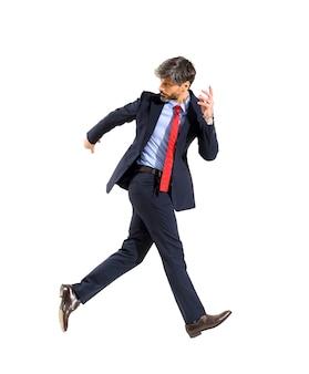 Giubilante uomo d'affari elegante di successo che cammina sull'aria guardando indietro sulla sua spalla in un'immagine concettuale dell'idioma isolato