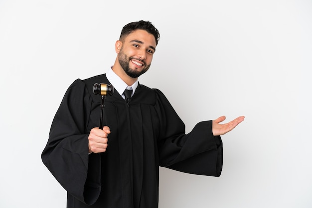 Giudice uomo arabo isolato su sfondo bianco estendendo le mani di lato per invitare a venire