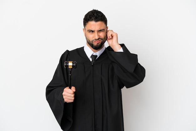 Giudice uomo arabo isolato su sfondo bianco frustrato e che copre le orecchie