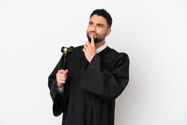 Giudice uomo arabo isolato su sfondo bianco avendo dubbi mentre guarda in alto