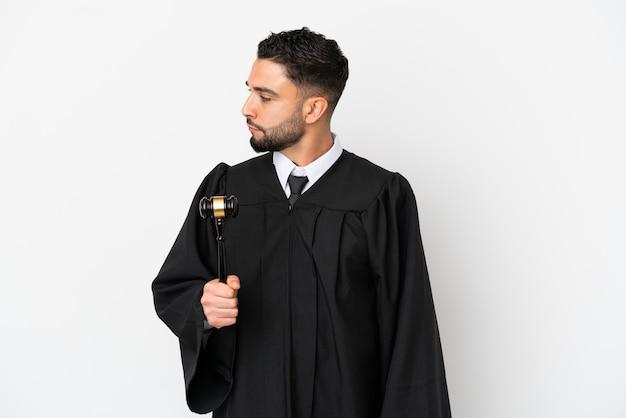 Giudice uomo arabo isolato su sfondo bianco guardando al lato