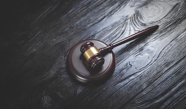 Martelletto del giudice sulla scrivania in legno nero.