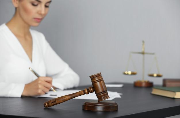 Martelletto del giudice e donna d'affari seduti a tavola