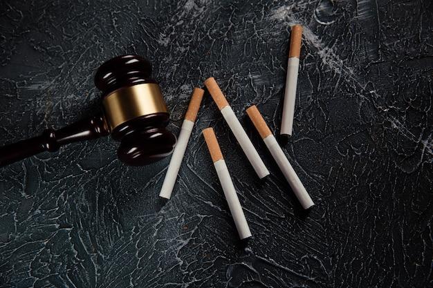 Giudice martelletto e sigarette sul tavolo grigio legge sul tabacco