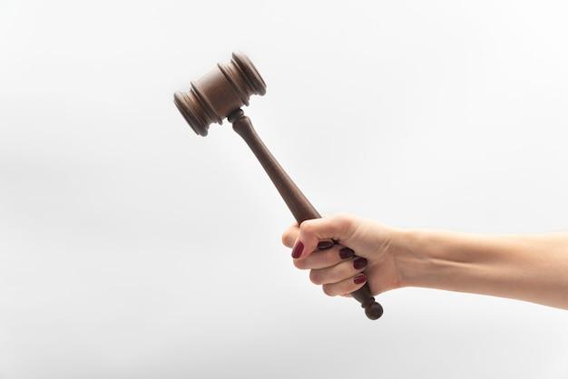 Martelletto del giudice in mano femminile sul muro bianco