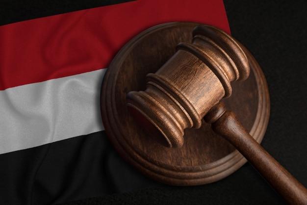 Giudice martello e bandiera dello yemen. diritto e giustizia nella repubblica dello yemen. violazione di diritti e libertà.