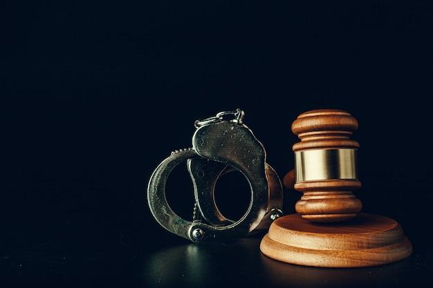 Giudice martelletto e manette su sfondo nero scuro