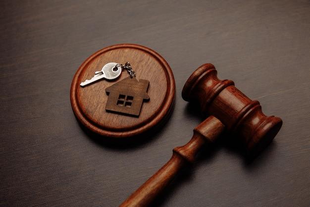 Martelletto del giudice e portachiavi a forma di due parti di casa divise su legno