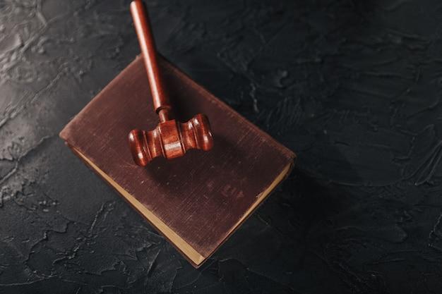 Martelletto del giudice e libro legale sul concetto di tavola, giustizia e diritto in legno.