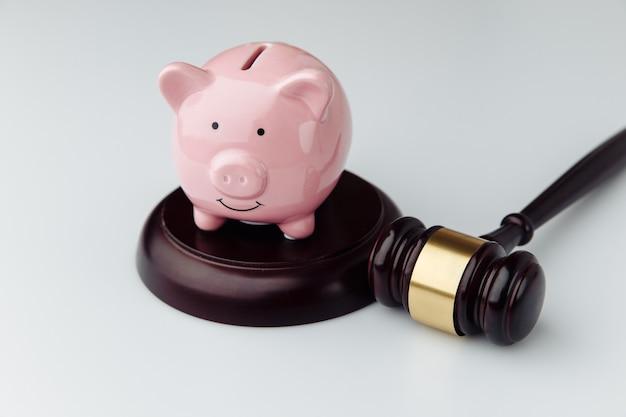 Martelletto del giudice e porcellino salvadanaio rosa su una scrivania bianca