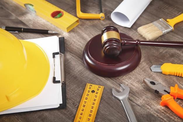 Martelletto del giudice, casco di sicurezza e strumenti di lavoro. diritto delle costruzioni
