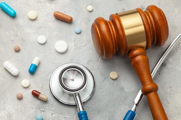 Giudice martelletto e stetoscopio con le pillole. la legge in medicina, la sentenza sulla colpa medica.