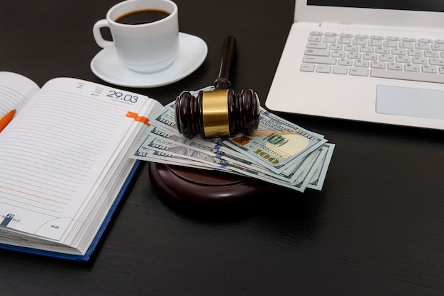 Martelletto del giudice con banconote in dollari, laptop e caffè