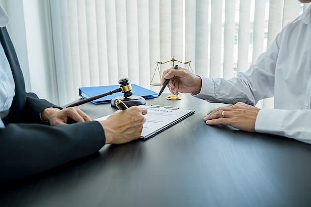 Martelletto del giudice con gli avvocati della giustizia che si riuniscono in gruppo presso lo studio legale. concetti di diritto e servizi legali.