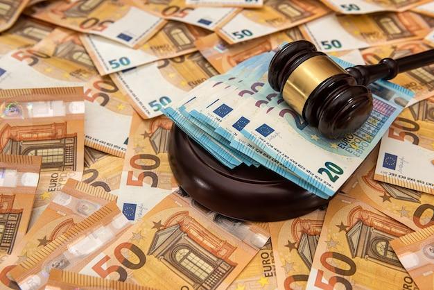 Martello del giudice su sfondo di 50 banconote in euro. diritto giudiziario