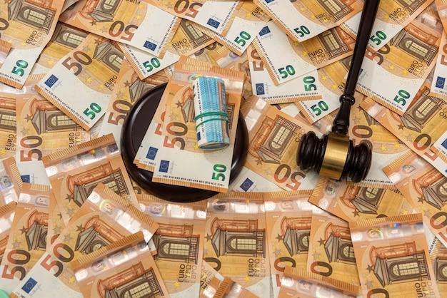 Martello del giudice su sfondo di 50 banconote in euro