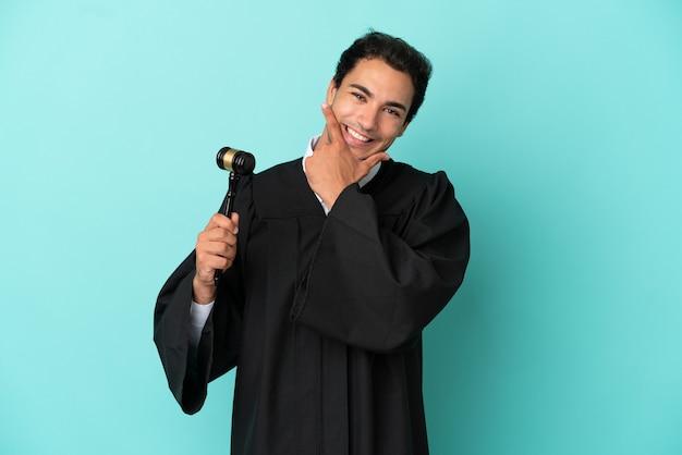 Giudice su sfondo blu isolato felice e sorridente