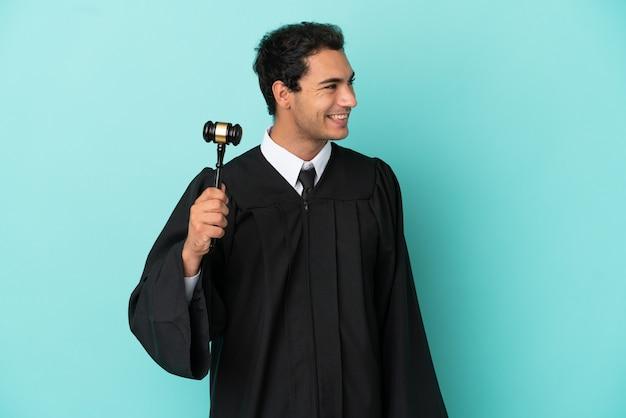 Giudice su sfondo blu isolato guardando di lato e sorridente