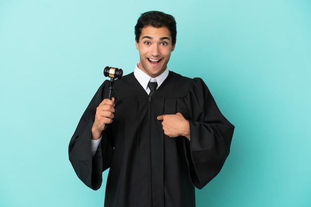 Giudice su sfondo blu isolato con espressione facciale a sorpresa