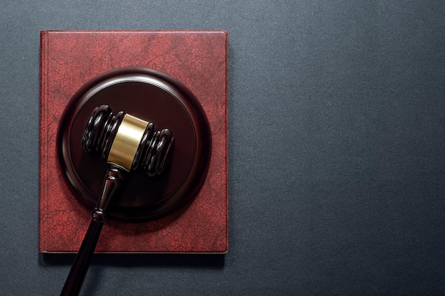 Martelletto e libro del giudice su fondo in pelle nera, vista dall'alto. concetto di diritto.