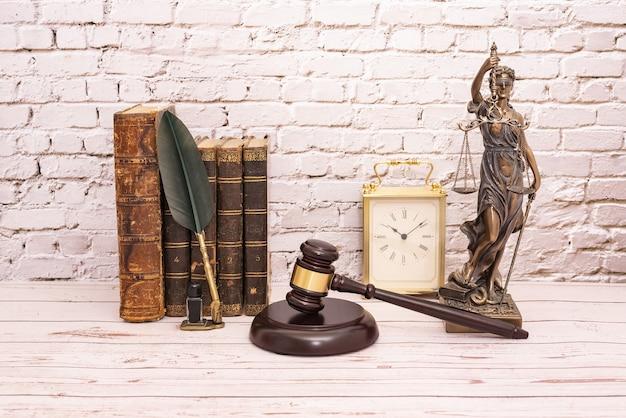 Martelletto del giudice e simbolo della giustizia con libro e orologio.