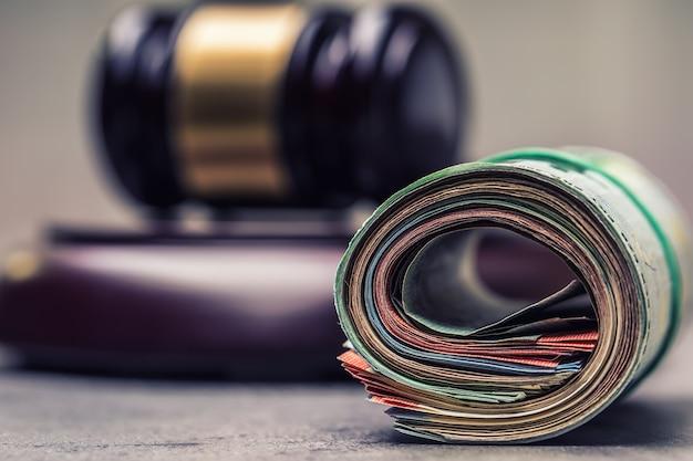 Martelletto del giudice. giustizia ed euro soldi. valuta dell'euro. martelletto di corte e banconote in euro arrotolate. rappresentanza della corruzione e concussione nella magistratura.