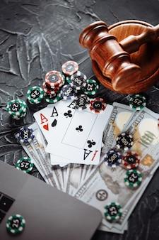 Martelletto di legno del giudice, fiches da poker, soldi e carte da gioco. nozione di diritto e regolamentazione del gioco d'azzardo.