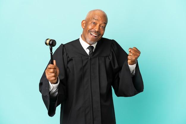 Giudice uomo anziano isolato su sfondo blu che celebra una vittoria nella posizione del vincitore