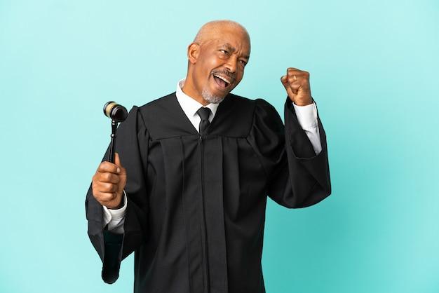 Giudice uomo anziano isolato su sfondo blu che celebra una vittoria