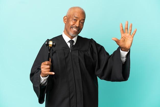 Giudice uomo anziano isolato su sfondo blu contando cinque con le dita