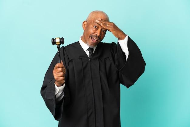 Giudice uomo anziano isolato su sfondo blu che fa un gesto a sorpresa mentre guarda di lato