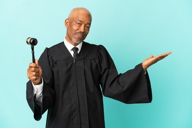 Giudice uomo anziano isolato su sfondo blu che estende le mani di lato per invitare a venire
