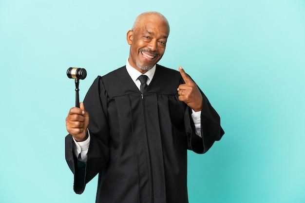 Giudice uomo anziano isolato su sfondo blu dando un gesto di pollice in alto