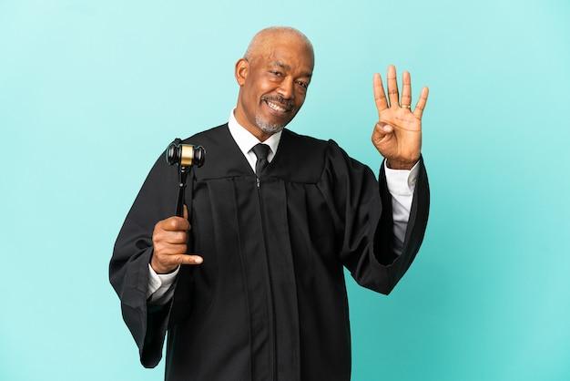 Giudice uomo anziano isolato su sfondo blu felice e contando quattro con le dita